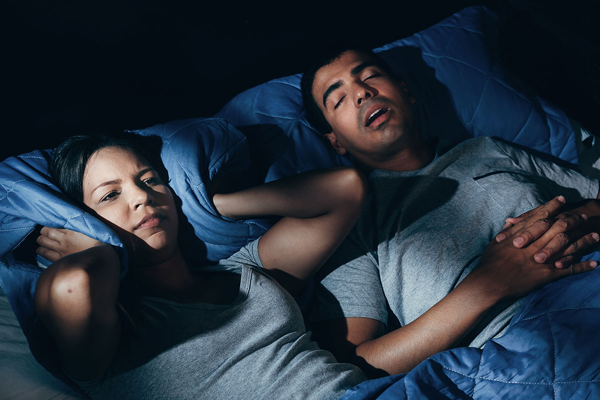 Women wide awake in bed with snoring partner