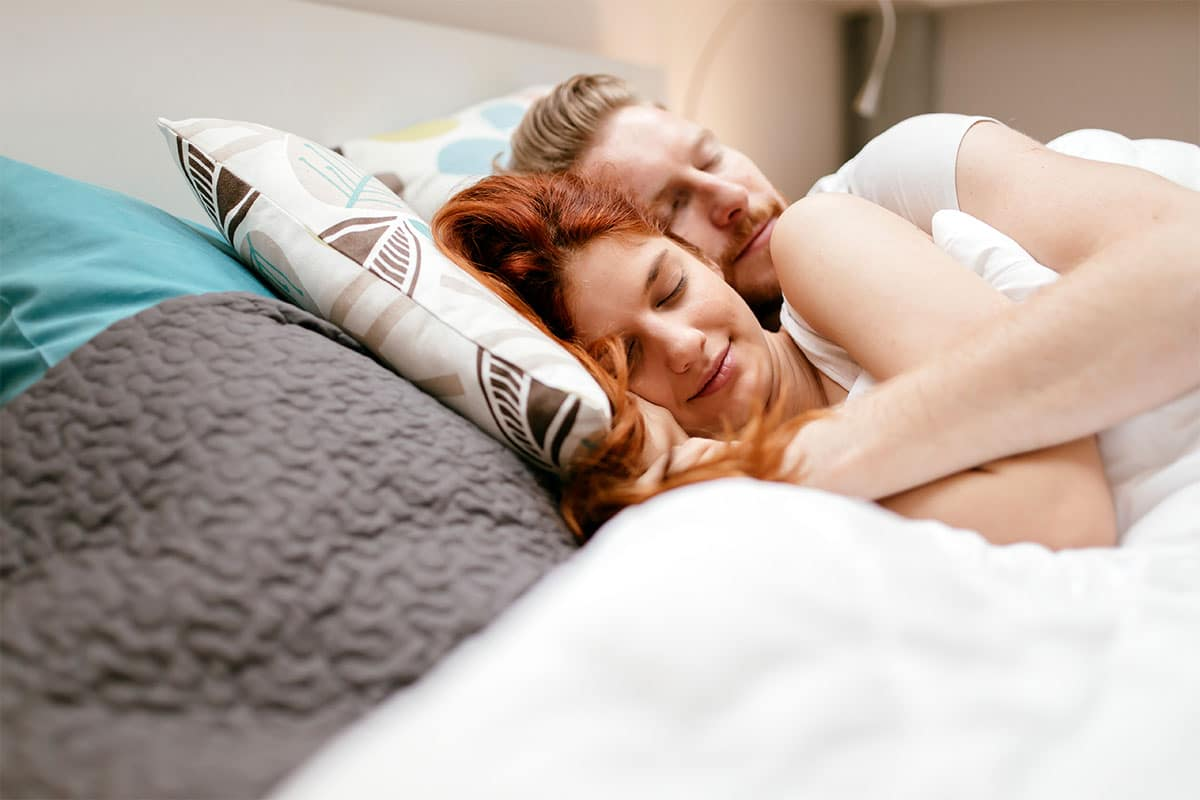 Sleep and the immune system - Healthy couple in bed.