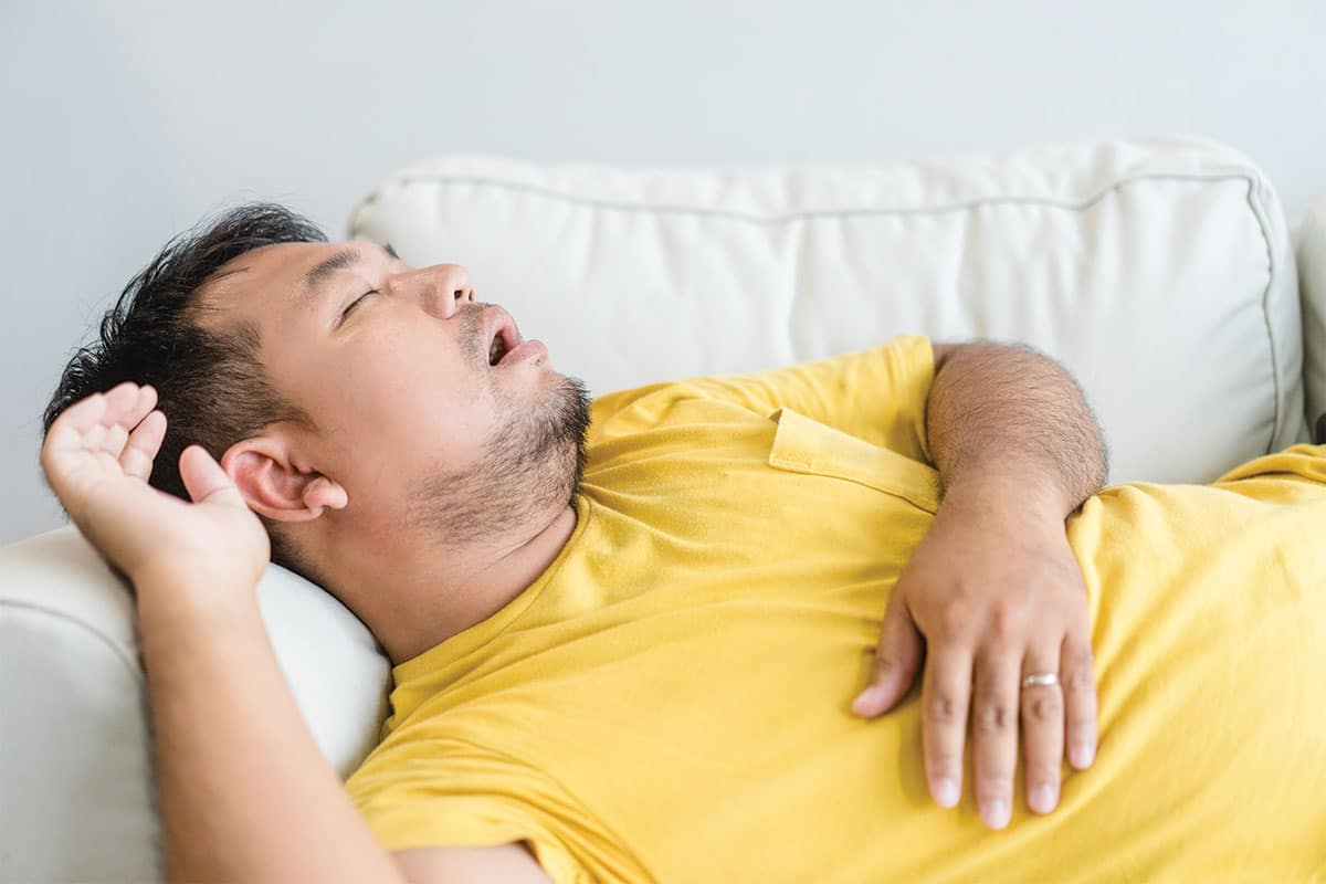 Why do people snore? Man snoring while sleeping on couch.